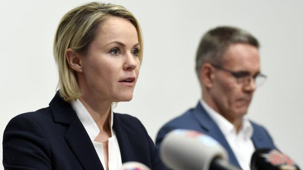 Eine Frau mit blonden Haaren informiert, im Vordergrund stehen Mikrofone.