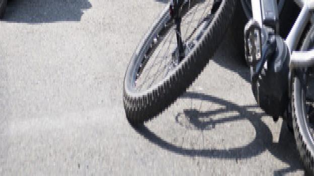 Sanitätsfachleute kümmern sich auf einer Strasse um einen verletzten E-Bike-Fahrer.