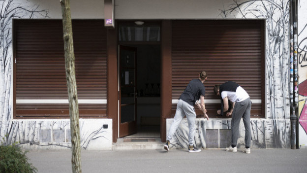 Zwei Männer lassen die Rollläden eines Geschäftes herunter.