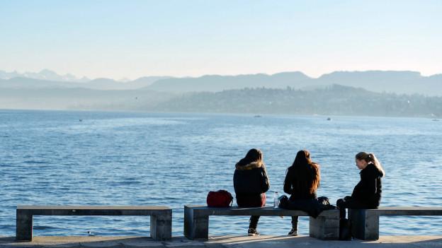 Drei Mädchen sitzen auf einer Bank am Zürcher Seebecken und geniessen die Sonne.