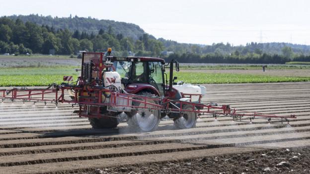 Ein Bauer arbeitet mit seinem Traktor auf dem Feld.