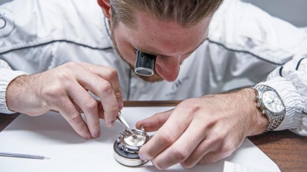 Uhrmacher mit Uhr, Lupe und Pinzette