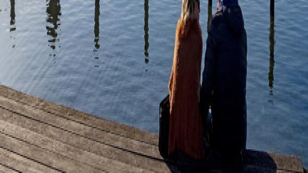 Menschen sitzen am Ufer des Greuifensees und geniessen die Sonne.