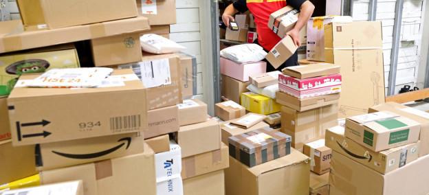 Ein Mitarbeiter einer Paketlieferfirma steht in einer Lagerhalle vor einem Stapel Paketen und scannt diese ein.