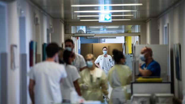 Aerzte und Pflegepersonal in einem Spital mit Gesichtsmasken.