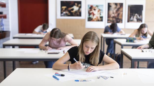 Schülerinnen sitzen weit verteilt in einem Klassenzimmer.