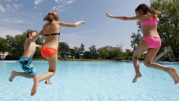 Drei Kinder springen im Freibad Letzigraben in Zürich ins Wasser.