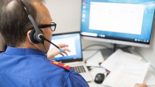 Polizist mit Headset vor einem Computer, vor sich Dokumente