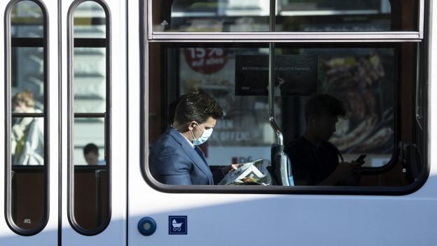 Ein Mann sitzt mit einer Schutzmaske in einem Zürcher Tram.