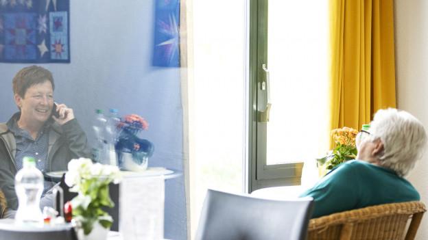 Eine Seniorin unterhält sich durch eine Trennscheibe mit einer Besucherin