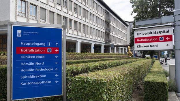 Der Eingang des Zürcher Universitätsspitals mit grossen Anzeigetafeln im Vordergrund.