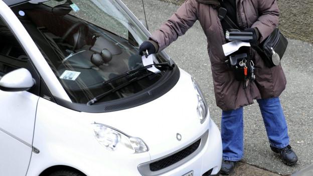 Eine Mitarbeiterin der Stadtpolizei Zürich steckt gerade einen Strafzettel unter eine Windschutzscheibe eines weissen Smarts.