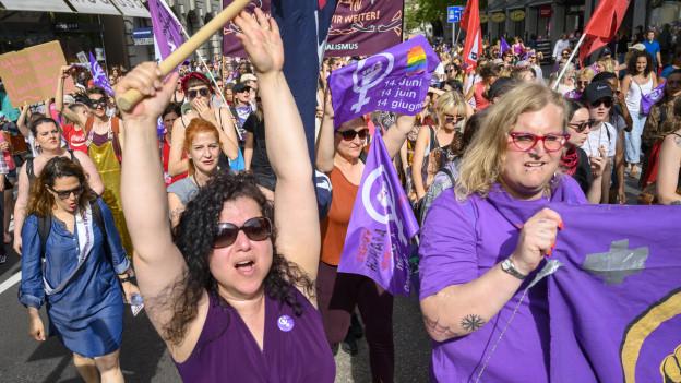 Frauen in lila und mit bunten Transparenten führen den Frauenstreikumzug durch die Stadt Zürich an (Aufnahme aus dem Jahr 2019).