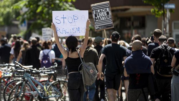 """Menschen in schwarzer Kleidung halten Transparente mit der Aufschrift """"Black Lives Matter"""" und """"Stop Racism"""" an einer Kundgebung am vergangenen Wochenende in der Stadt Zürich in die Höhe."""