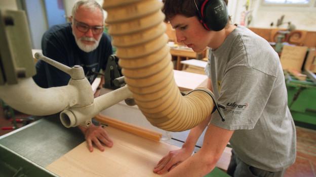 Ein Jugendlicher mit Ohrschutz wird vom Lehrmeister beim Zuschneiden eines Holzbretts angeleitet.