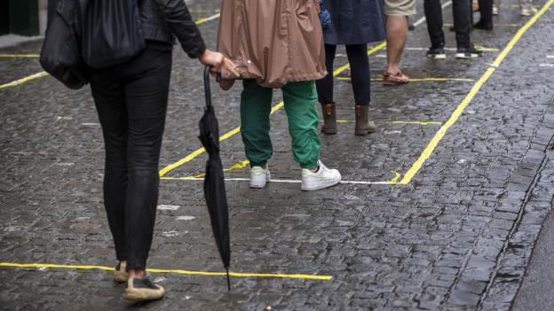 Menschen stehen in einer Reihe mit 2 Meter Abstand Markierungen am Boden.