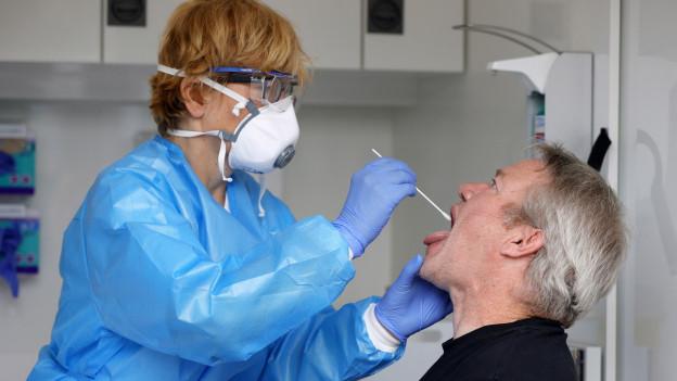 Frau mit Maske steckt Mann Röhrchen in Hals