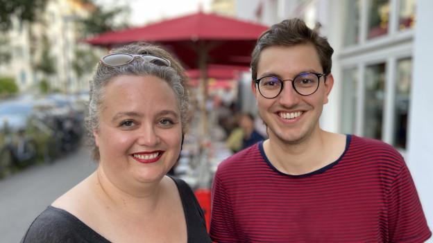 Der neue Stadtzürcher SP-Co-Präsident Oliver Heimgartner steht rechts von Co-Präsidentin Liv Mahrer vor einer Strassenszene mit Gartenrestaurant im Hintergrund.