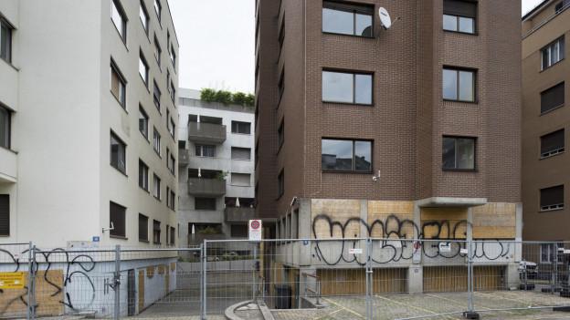 zwei schmucklose Mehrfamilienhäuser mit Graffitti