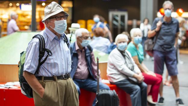 Eine Gruppe Menschen, alle mit Hygienemaske, wartet am Bahnhof auf den Zug.