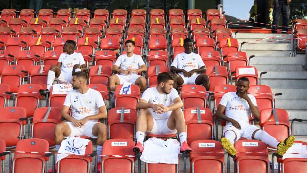 FCZ Spieler sitzen auf roten Tribünen-Stühlen, mit Abstand