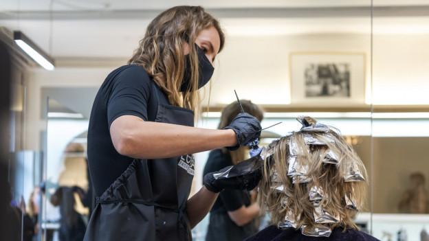 Eine Coiffeuse trägt bei ihrer Arbeit eine Maske