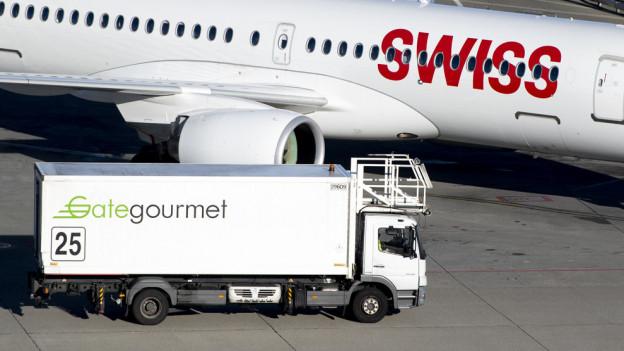 Ein Lastwagen von GateGourmet steht neben einem Flugzeug