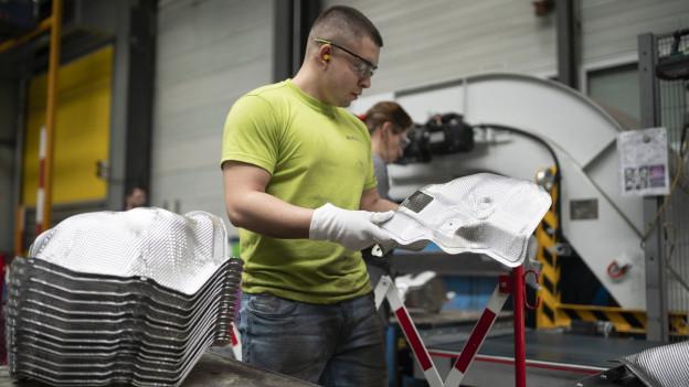 Ein Arbeiter mit Metallbestandteilen in der Produktionsstätte von Autoneum im Kanton St. Gallen.