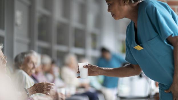 Eine Mitarbeitende eines Altersheim reicht einer Bewohnerin gerade ein Getränk zur Abkühlung.