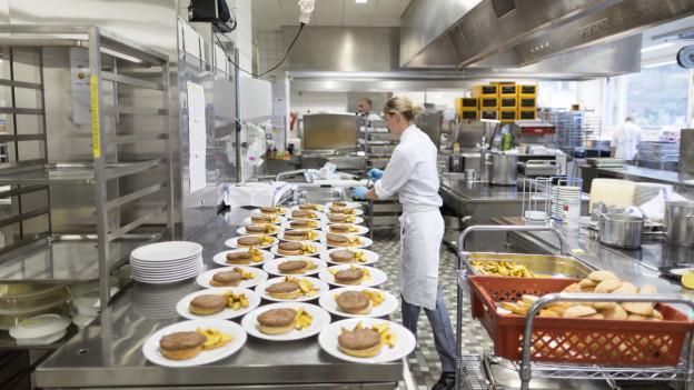 In einer Spitalküche werden Hamburger auf Teller verteilt.