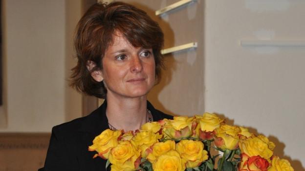 Purtret da Cornelia Camichel Bromeis cun rosas melnas.
