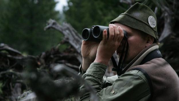 Chatschadur cun binoculars en il guaud.