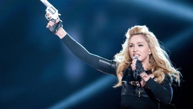 Madonna duran in concert vi da chantar cun ina pistola enta maun.