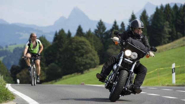 In motociclist ed in um cun velo.