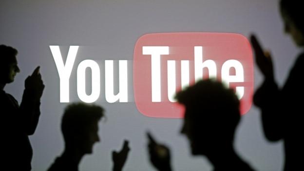 Persunas poseschan avant il logo da Youtube, cun lur telefonin enta maun.