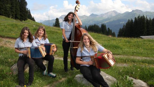Trais giuvnas cun lur instruments sin in'alp