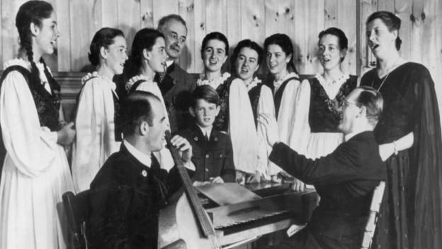 Famiglia che stat davos in calavazin e chanta chanzuns popularas.