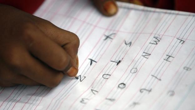 In uffant scriva il alfabet sin in pupi.