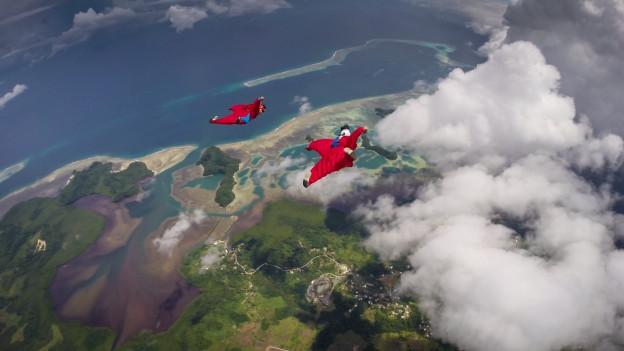 Duas persunas che sgolan cun wingsuit.