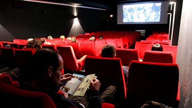 Sala d'in kino cun pliras persunas.