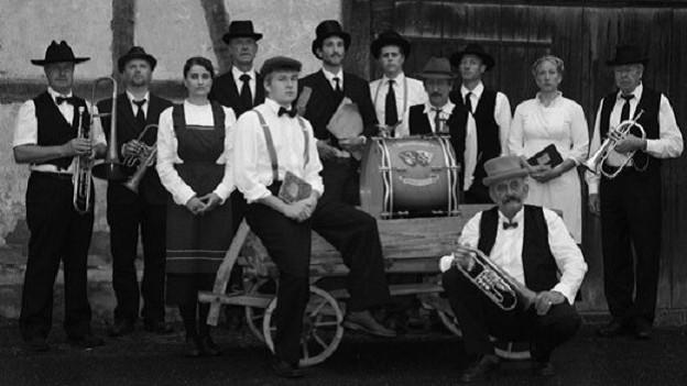 Foto da gruppa da la musica da Schlatt cun costums vegls en stil vegl.