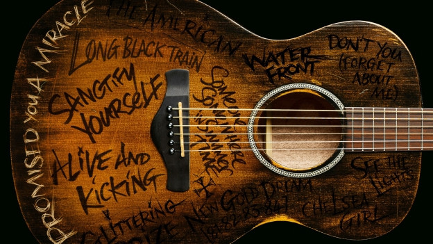 Ina gitarra cun inscripziuns sin il cover da la single.