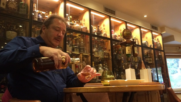 Purtret da Claudio Bernasconi co el derscha en in glas Whisky.