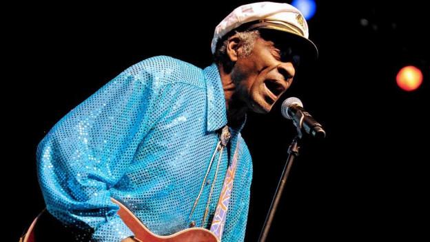 Chuck Berry chanta e suna gitara ad in concert.