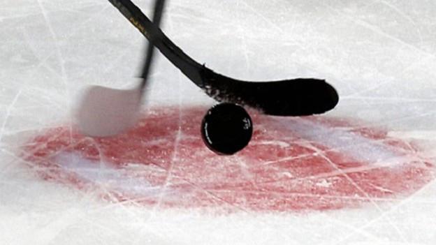 In puck da hockey cun dus bastuns da hockey al bully