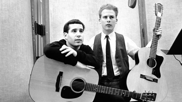 Paul Simon e Art Garfunkel cun sias gitarras.