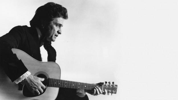 Purtret da Johnny Cash cun sia gitarra.