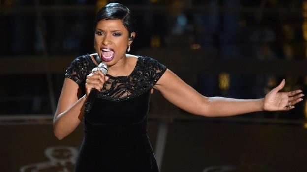 Jennifer Hudson cun il microfon vid chantar.