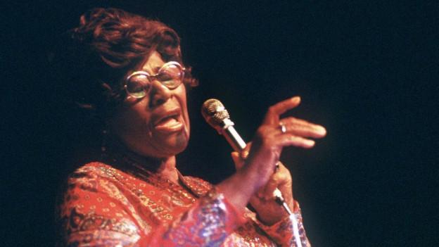 Eine dunkelhäutige Sängerin mit Brille.