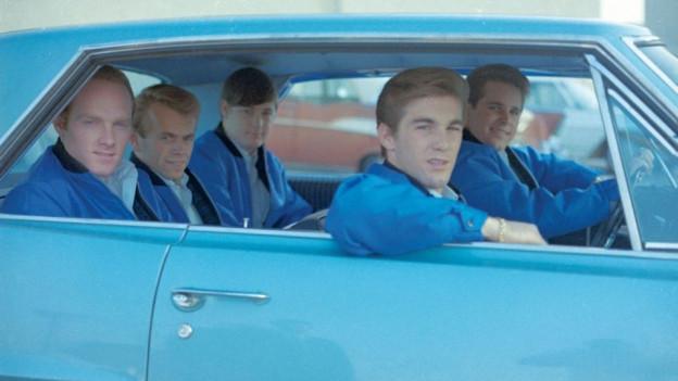 Ils tschintg Beach Boys sesan en in auto blau.
